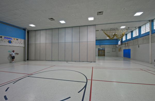 Manual and electrical train panel folding wall inside a school gymnasium