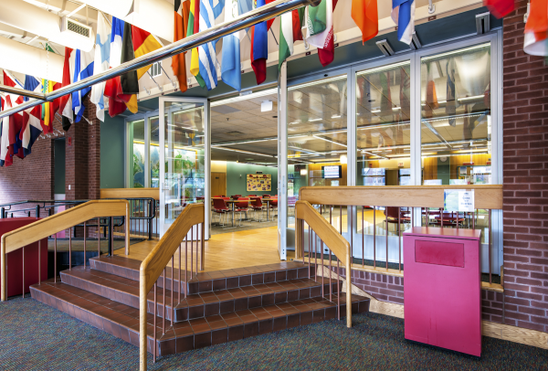 Photo of movable glass walls and folding doors separating a study hall area from corridor space