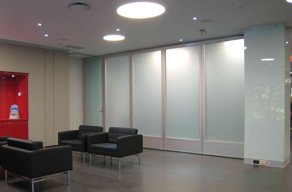 Glass folding doors clear separation for office spaces for Folding glass wall